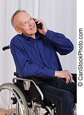Disabled man talking on the phone - Disabled man sitting in...