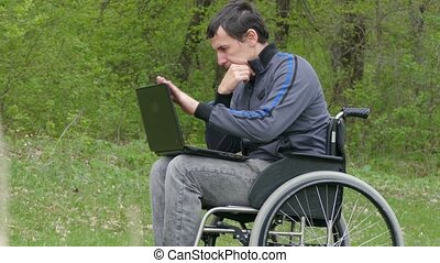 disabled man thinks problems wheelchair with a laptop in a wheelchair working on  green background nature