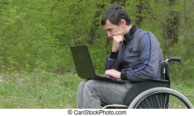 disabled man thinks problems wheelchair with a laptop in working on  green background nature