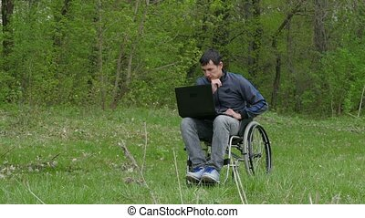 disabled man thinks tired of break problems wheelchair with a laptop in a wheelchair working on nature green background
