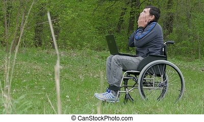 disabled man thinks tired of break problems wheelchair with laptop in wheelchair working on nature green background