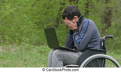 disabled man thinks tired of break problems wheelchair with laptop in working on nature green background