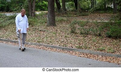Disabled Man Using Cane - Crippled disabled man walks at the...