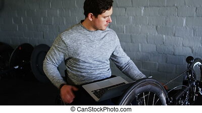 Disabled man using laptop while repairing wheelchair 4k -...