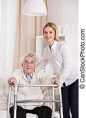 Disabled man using walking frame