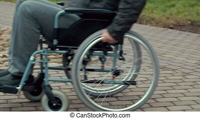 Disabled man using wheelchair on path