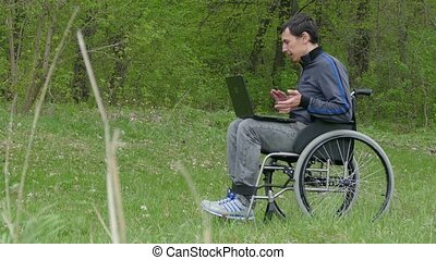 disabled man video chat conversation wheelchair with a laptop in a wheelchair working on nature green background