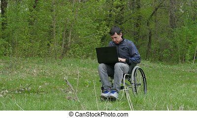 disabled man wheelchair with a laptop in a wheelchair working on nature green background