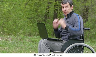disabled man wheelchair with a laptop in wheelchair working on nature green