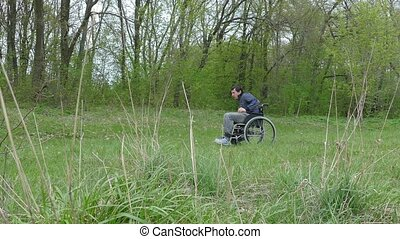 disabled man wheelchair with laptop in wheelchair working on nature green background