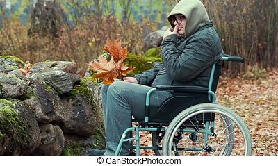 Disabled man with autumn leaves