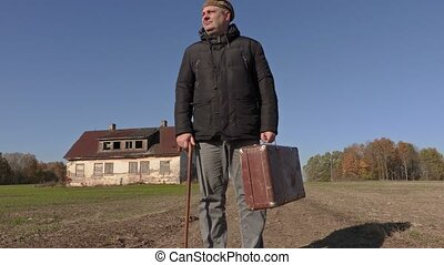 Disabled man with cane and suitcase walking to the home