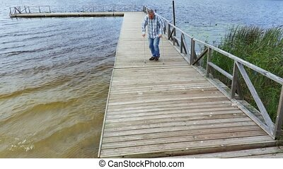 Disabled man with crutches at the lake