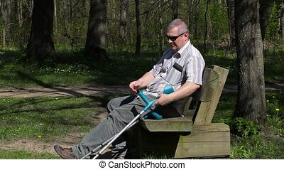 Disabled man with crutches enjoy nature on bench in the park