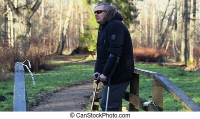 Disabled man with crutches on wooden bridge