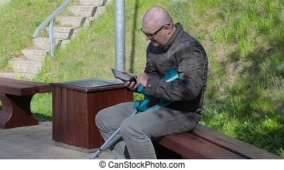 Disabled man with crutches sitting on bench and using tablet PC