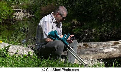 Disabled man with crutches using tablet PC near river