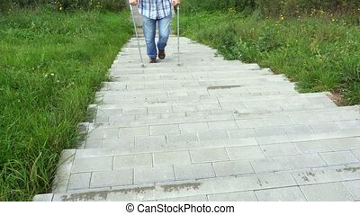 Disabled man with crutches walking on footway