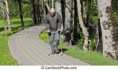 Disabled man with crutches walking on path in the park