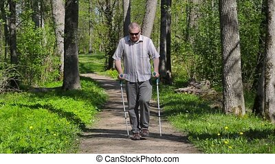 Disabled man with crutches walking