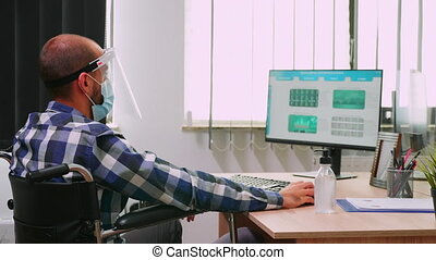 Disabled businessman sitting in wheelchair wearing face mask and visor against coronavirus disinfecting hands before checking financial data in business office. Freelancer respecting social distance