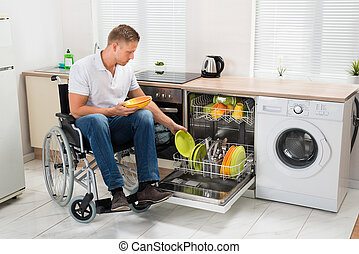 Disabled Man Working In Kitchen - Young Disabled Man Sitting...