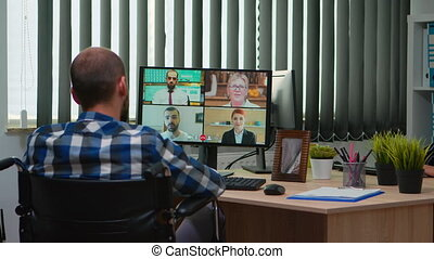 Handicapped disabled manager in wheelchair talking during videocall having online conference in business office. Paralysed, immobilized freelancer working in financial company using modern technology.