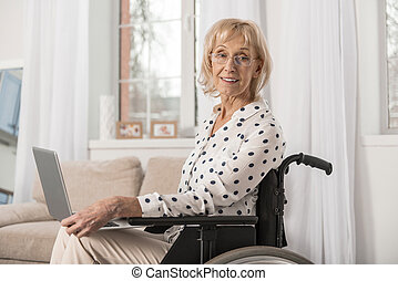 Disabled mature woman working online