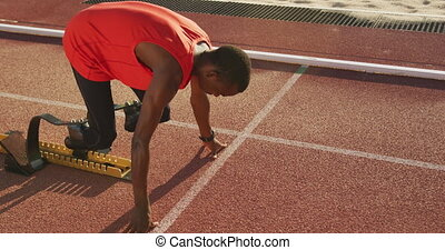 Fit, disabled mixed race male athlete with prosthetic legs on a running track at an outdoor sports stadium starting a race from the starting blocks, in slow motion