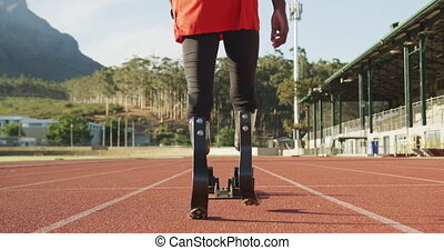 Fit, disabled mixed race man with prosthetic legs walking on racing track towards starting blocks in slow motion