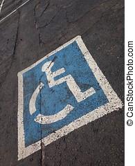 Disabled parking sign painted on asphalt.