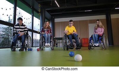 Group of positive people with disabilities playing bocce game adapted for players confined to wheelchairs. Teen boy with cerebral palsy throwing ball while playing in pair with friend against women