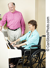 Disabled Pianist - Disabled woman plays piano while an...