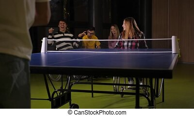 Adult redhead woman in wheelchair and man with cerebral palsy playing table tennis while positive young people with disabilities communicating and watching game on background