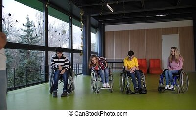 Cheerful people with disabilities in wheelchairs playing boccia game indoors. Adult woman player making successful throw and everyone applauding her with joy, socializing gaming activity for disabled