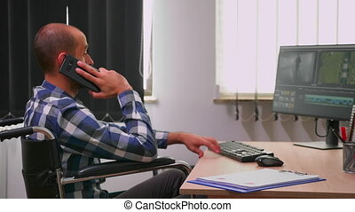 Disabled professional videographer speaking on phone during editing a video project creating content sitting in wheelchair in modern company office. Creator blogger working from photo studio.