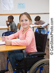 Disabled pupil smiling at camera in classroom at the ...