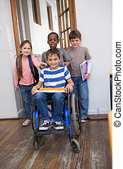 Disabled pupil with his friends in classroom at the...