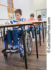 Disabled pupil writing at desk in classroom at the ...