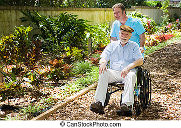 Disabled Senior Enjoying Garden - Disabled senior man being...
