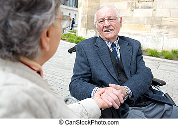 disabled senior man holding his wifes hand