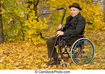 Disabled senior man in a wheelchair sitting in his overcoat...