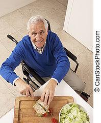 Disabled Senior Man Making Sandwich In Kitchen