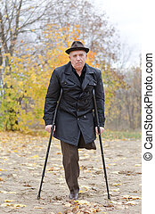 Disabled senior man on crutches