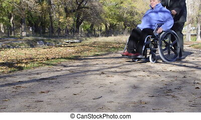 Disabled senior person in wheelchair with caregiver