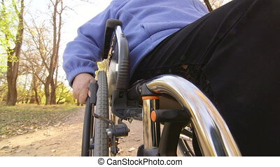 Disabled senior person turning wheels of wheelchair, camera...