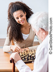 Image of carer and disabled senior with hobby