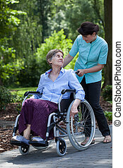Disabled senior woman and nurse in park