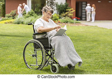 Disabled senior woman in the wheelchair reading book in the garden