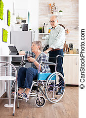 Disabled senior woman in wheelchair using tablet computer in kitchen with husband near. Paralysied handicapped old elderly person using modern communication online internet web techonolgy.